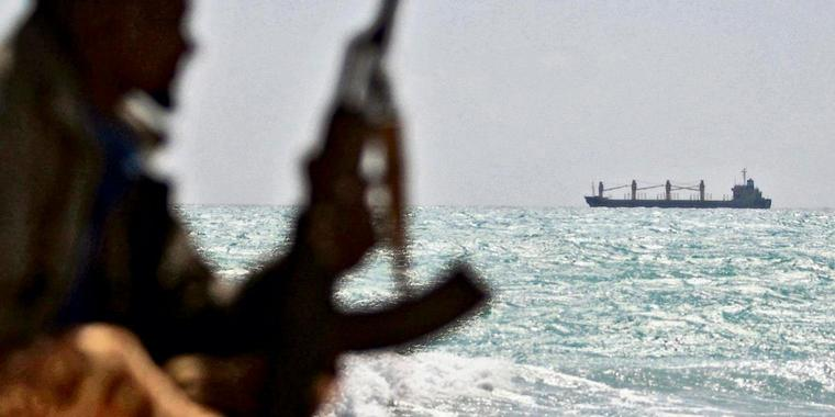 Photo made on January 7, 2010 shows an armed Somali pirate along the coastline while the Greek cargo ship, MV Filitsa, is seen anchored just off the shores of Hobyo town in northeastern Somalia where its being held by pirates. A six-nation east African regional bloc on February 1, 2010 urged Somalia's two breakaway regions of Puntland and Somaliland to jointly battle Islamist militia which it said had extended to the areas.  AFP PHOTO/ MOHAMED DAHIR
