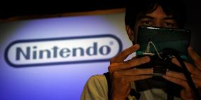 Ein Besucher der Electronic Entertainment Expo in Los Angeles hält eine Nintendo-pielekonsole in der Hand.