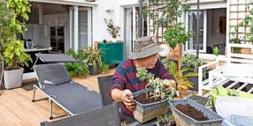Side view of senior male pensioner in casual clothes and hat planting seedlings in pot while sitting at table in garden near house Copyright: xInigoxCallesx Senioren und Terasse