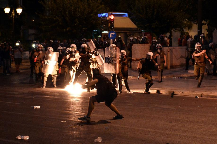 A protester hurls petrol bomb on riot police in central Athens, during an anti-austerity protest on July 15, 2015. Anti-austerity protesters hurled petrol bombs at police in front of Greece's parliament on July 15, as lawmakers began debating deeply unpopular reforms needed to unlock a new eurozone bailout. Riot police responded with tear gas against dozens of hooded protesters who set ablaze parts of Syntagma square in central Athens. AFP PHOTO/ LOUISA GOULIAMAKI