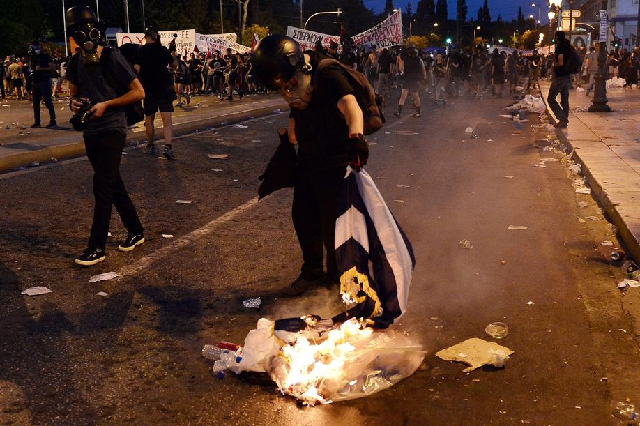 A protester burns a Greek flag in central Athens, during an anti-austerity protest on July 15, 2015. Anti-austerity protesters hurled petrol bombs at police in front of Greece's parliament on July 15, as lawmakers began debating deeply unpopular reforms needed to unlock a new eurozone bailout. Riot police responded with tear gas against dozens of hooded protesters who set ablaze parts of Syntagma square in central Athens. AFP PHOTO/ LOUISA GOULIAMAKI