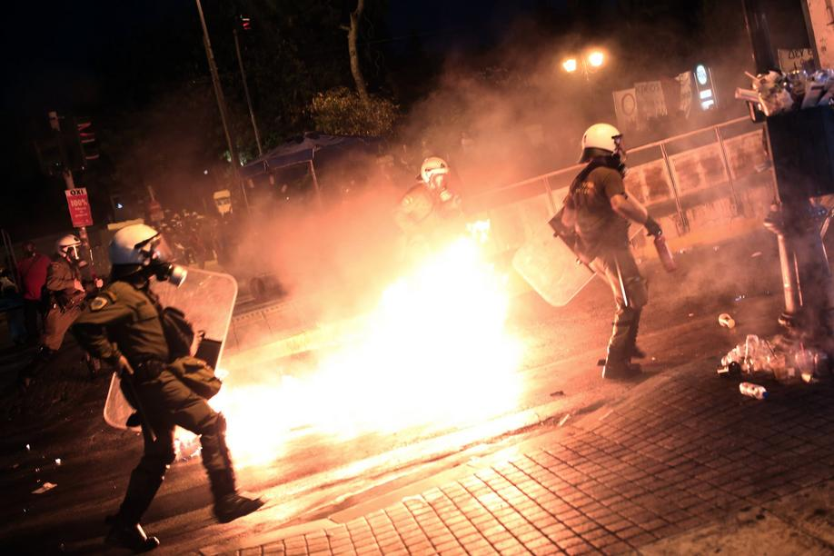 Riot policemen run after protesters throwing petrol bombs in central Athens, during an anti-austerity protest on July 15, 2015. Anti-austerity protesters hurled petrol bombs at police in front of Greece's parliament on July 15 as lawmakers began debating unpopular reforms needed to unlock a new eurozone bailout. Riot police responded with tear gas against dozens of hooded protesters who set ablaze parts of Syntagma square in central Athens AFP PHOTO / ANGELOS TZORTZINIS
