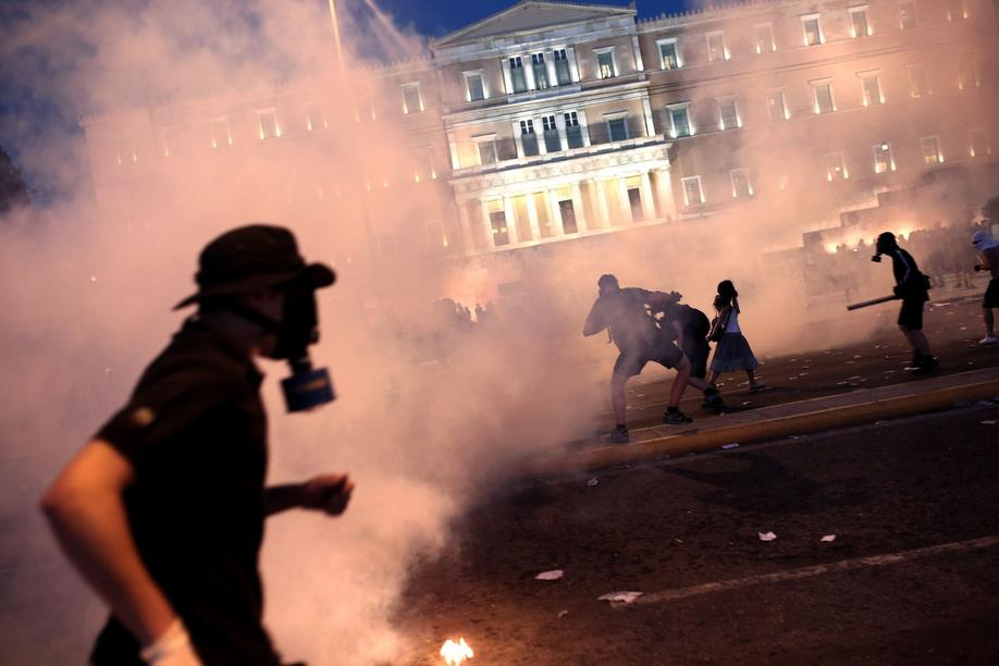A protester clashes with riot police in front of the Greek Parliament in Athens on July 15, 2015. Anti-austerity protesters hurled petrol bombs at police in front of Greece's parliament on July 15, as lawmakers began debating deeply unpopular reforms needed to unlock a new eurozone bailout. Riot police responded with tear gas against dozens of hooded protesters who set ablaze parts of Syntagma square in central Athens. AFP PHOTO / ANGELOS TZORTZINIS