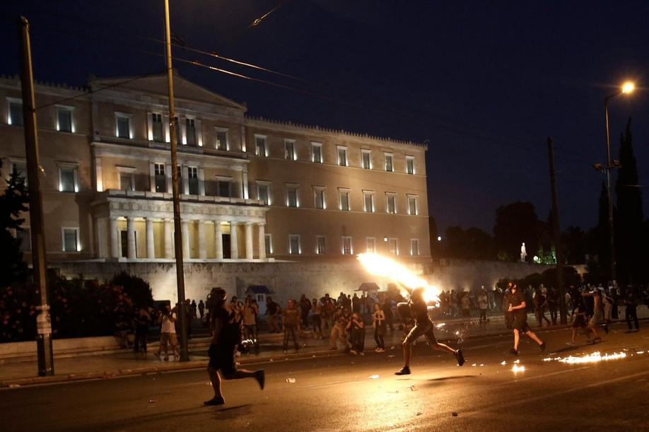 epa04848232 Protesters throw petrol bombs to policemen in front of the parliament during a demonstration against the prior actions expected to be voted by lawmakers, in Athens, Greece, 15 July 2015. A debate on reforms that are key to a preliminary agreement with creditors to keep Greece out of bankruptcy takes place in the country's legislature, but fissures were already beginning to show among the ruling SYRIZA party. EPA/YANNIS KOLESIDIS +++(c) dpa - Bildfunk+++