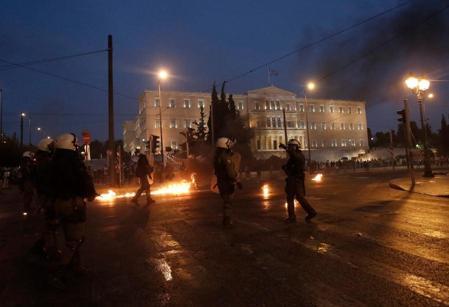 epa04848269 Greek policemen try to avoid a petrol bomb thrown by protester during a demonstration against the prior actions expected to be voted by lawmakers, outside the parliament in Athens, Greece, 15 July 2015. A debate on reforms that are key to a preliminary agreement with creditors to keep Greece out of bankruptcy takes place in the country's legislature, but fissures were already beginning to show among the ruling SYRIZA party. EPA/YANNIS KOLESIDIS +++(c) dpa - Bildfunk+++