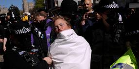 """A topless protester who shouted """"save the planet"""", is taken away by police officers after they put a cover over her body outside Windsor Castle during the funeral of Britain's Prince Philip in Windsor, England, Saturday, April 17, 2021. Philip died April 9 at the age of 99 after 73 years of marriage to Britain's Queen Elizabeth II. Coronavirus restrictions mean there will be only 30 mourners for the service, including the widowed queen, her four children and her eight grandchildren. (AP Photo/Matt Dunham)"""