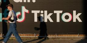 BERLIN, GERMANY - SEPTEMBER 21: A young man holding a smartphone walks past an advertisement for social media company TikTok on September 21, 2020 in Berlin, Germany. U.S. President Donald Trump has given preliminary approval for Oracle, Walmart and other investors to take over TikTok and create a new U.S.-based company called TikTok Global. (Photo by Sean Gallup/Getty Images)